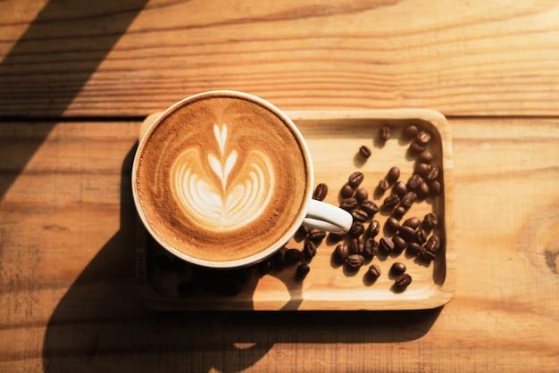 Чашка кофе с рисунком сердца в белой чашке на фоне деревянный стол