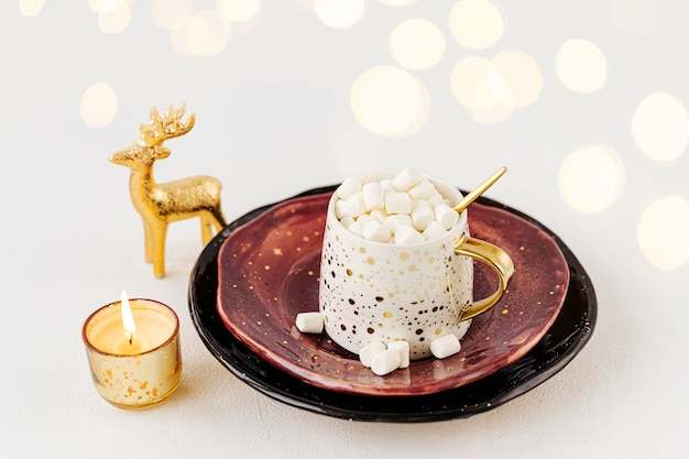 흰색 바탕에 마시멜로와 크리스마스 장식이 있는 커피 한 잔. 휴일 개념입니다.