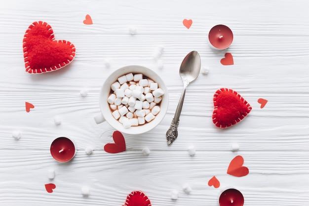 Чашка кофе с зефиром, декоративные сердца и свечи на белом столе