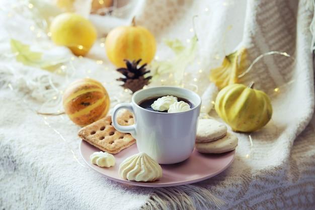 メレンゲクッキーカボチャとコーヒーのカップは、暖かい格子縞の照明に家の快適さの概念を残します