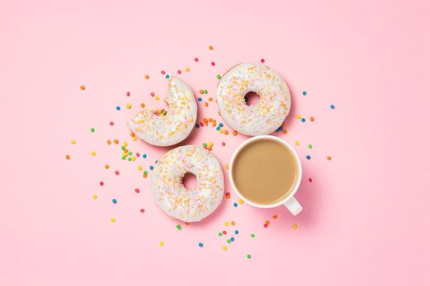 ミルク、ピンクの背景に新鮮なおいしい甘いドーナツとコーヒーカップ。ファーストフード、ベーカリー、朝食、お菓子の概念。ミニマリズム。フラット横たわっていた、トップビュー、コピースペース。