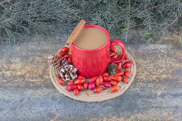 大理石の背景にローズヒップと松ぼっくりとコーヒーのカップ。高品質の写真