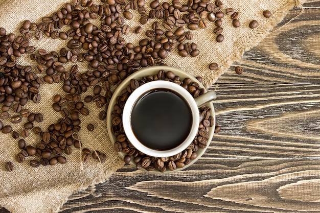 黄麻布の上に散らばったコーヒー豆と一杯のコーヒー