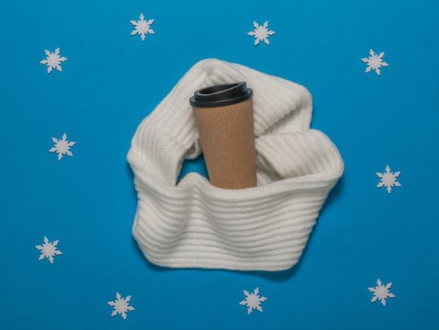 雪片の入ったスカーフに包まれた一杯のコーヒー。冬の気分。