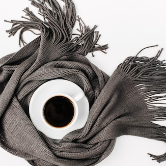 Чашка кофе, завернутая в шарф. осенняя или зимняя концепция. плоская планировка, вид сверху
