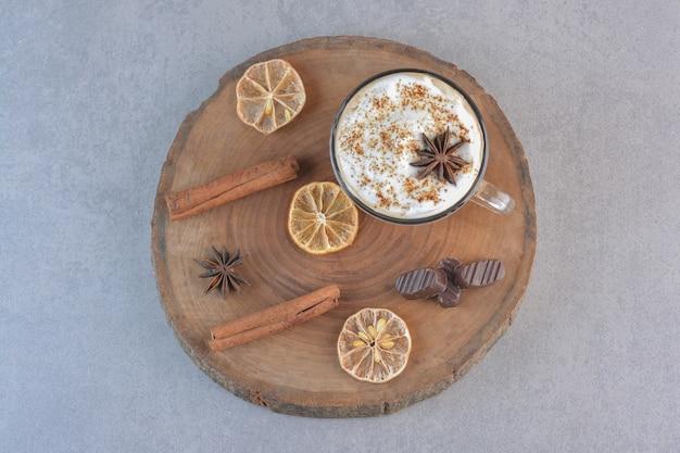 나무 판자에 크림 커피 한 잔과 계피 스틱.