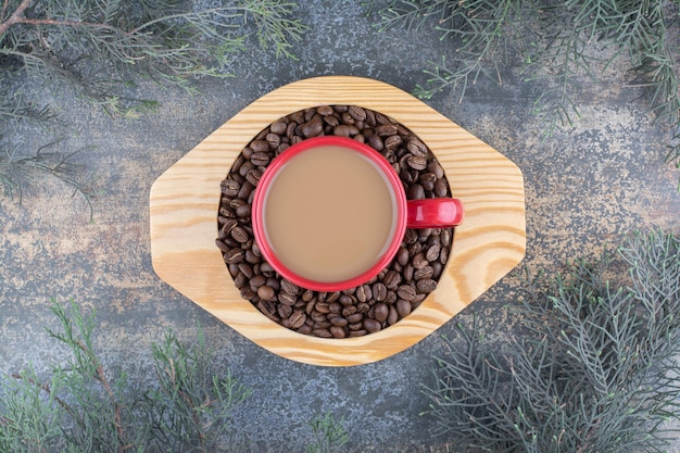 木の板にコーヒー豆と一緒に美味しいコーヒーを一杯。高品質の写真