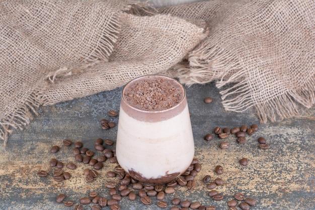 大理石のコーヒー豆とおいしい飲み物のカップ。