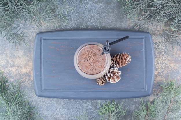 暗いボードに松ぼっくりとわらを入れたおいしい飲み物のカップ。高品質の写真