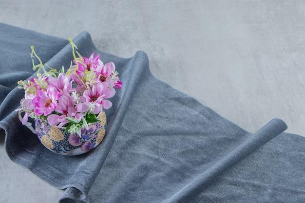 흰색 바탕에 직물 조각에 꽃 한 컵. 고품질 사진
