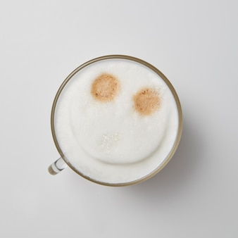 Чашка ароматного капучино с улыбающимся лицом на сером фоне с копией пространства. верхний