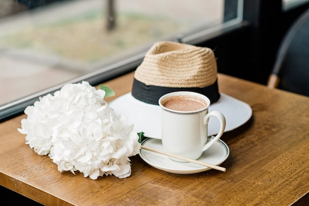 Чашка ароматного горячего какао с белыми цветами гортензии и шляпа на столе в кафе. мягкий выборочный фокус.