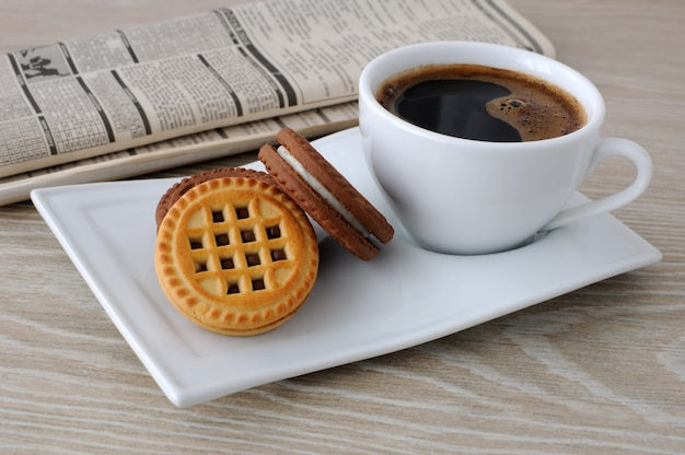 Чашка свежесваренного кофе и печенье на столе с газетой