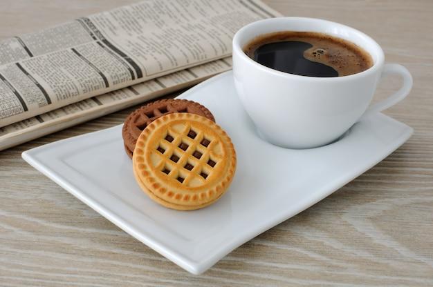 신문이 있는 탁자 위에 갓 내린 커피와 비스킷