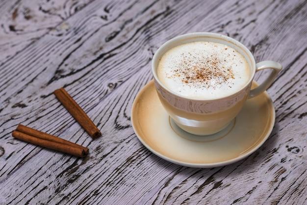 Чашка свежего кофе с палочками корицы на деревянном столе