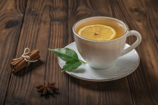 소박한 나무 테이블에 레몬을 넣은 신선한 녹차 한 잔. 건강에 도움이 되는 상쾌한 음료.