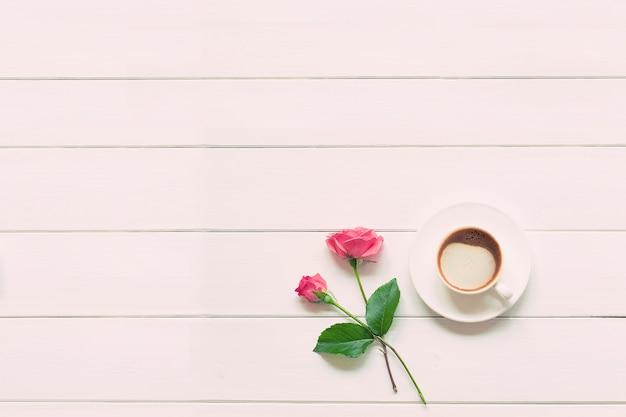 Чашка свежего горячего капучино с розовыми розами на белом деревянном столе