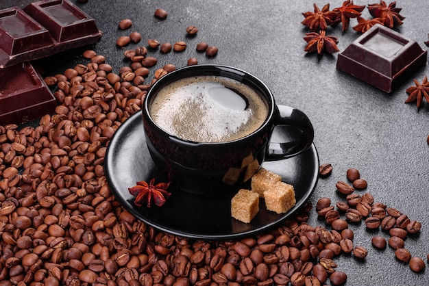 Чашка свежего ароматного утреннего кофе для веселого начала дня. красивая кофейная чашка с кофе на темном столе