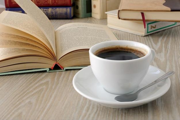 책이 있는 탁자 위에 갓 내린 커피 한 잔