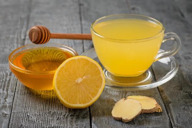 木製のテーブルにジンジャールートドリンクと蜂蜜のカップ。ウイルスと戦うためのツール。風邪の治療薬。