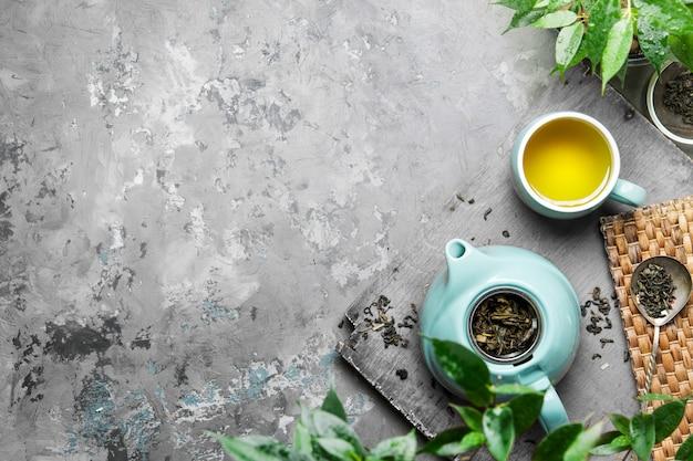 灰色のコンクリートの背景に青いカップで緑茶のカップ。