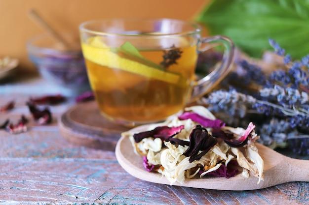 Чашка зеленого чая с цветами полезных трав и сухими лимонными лепестками полезных растений.