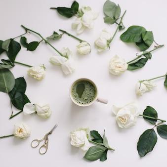 上から白い景色に白いバラと緑茶のカップ。フラットレイ、上面図、コピースペース。