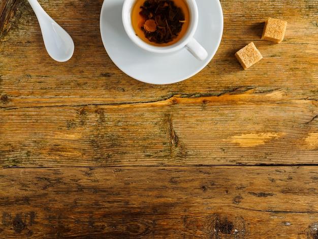Чашка травяного чая, ложка и кубики сахара на старой изношенной доске.
