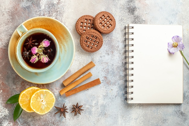 白いテーブルの上のハーブティービスケットとシナモンライムレモンスライスとノートブックのカップ