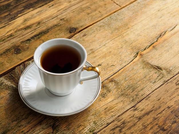 Чашка травяного чая на старой изношенной доске