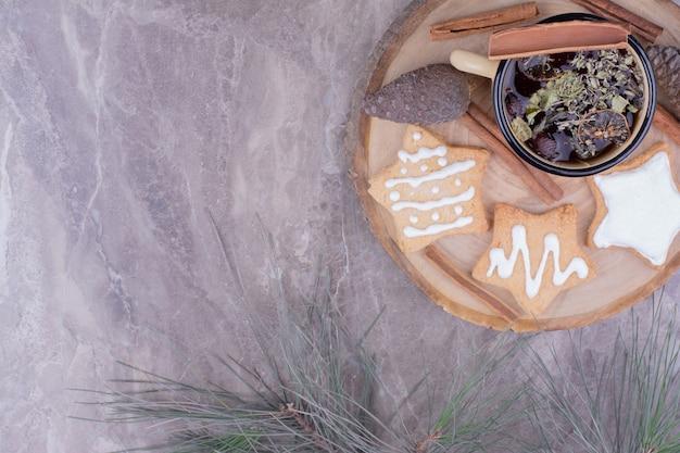 木の板にジンジャーブレッドとハーブティーのカップ