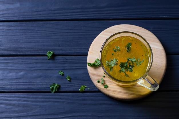 Чашка горячего куриного бульона с зеленью на деревянной доске. вид сверху. Premium Фотографии