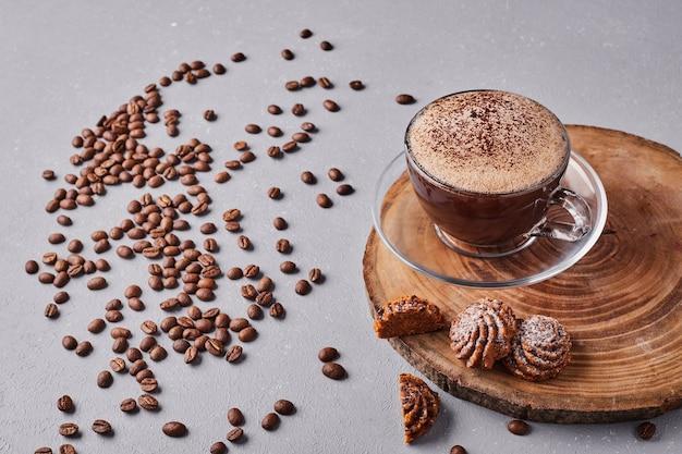 Чашка горячего шоколада с печеньем вокруг.