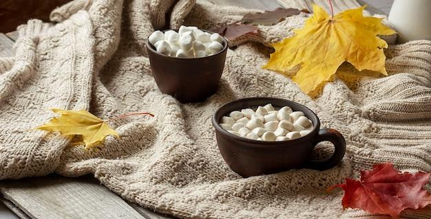Чашка горячего какао с зефиром стоит на уютном вязаном пледе.