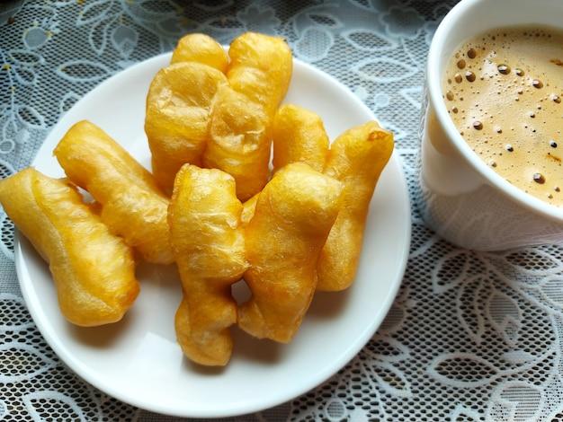 뜨거운 커피 한잔과 튀긴 반죽 스틱 patongko 테이블에