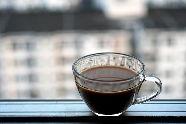 높은 건물 창가에서 아침에 뜨거운 커피 한 잔