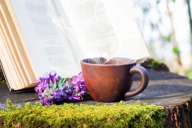 開いた本の横にある切り株の森の中でホットコーヒーのカップ。森で休む。野生の森の中で本を読む