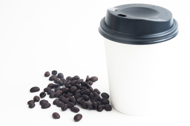 白い背景に焙煎コーヒー豆とブランドまたはロゴのための熱いコーヒーの一杯のモックアップ