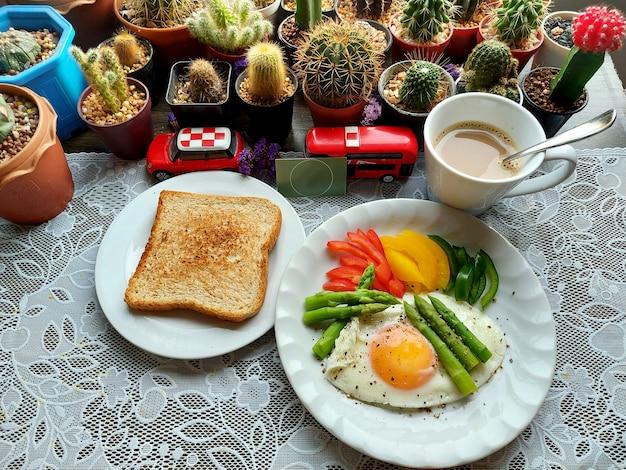 全粒粉トーストのスライスと白いプレートに野菜と目玉焼きとホットコーヒーのカップ