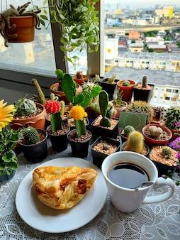 サボテンと多肉植物の背景にチキンパイとホットコーヒーのカップ