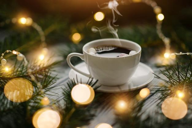 Чашка горячего кофе с зефиром среди еловых веток и огней праздничных гирлянд. зимняя композиция с выборочным фокусом.