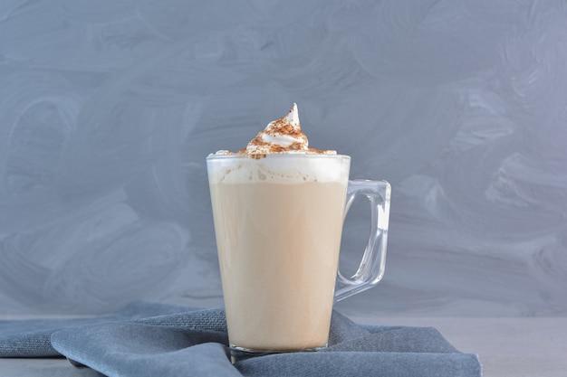 파란색 천에 카카오로 장식된 뜨거운 맛있는 커피 한 잔.