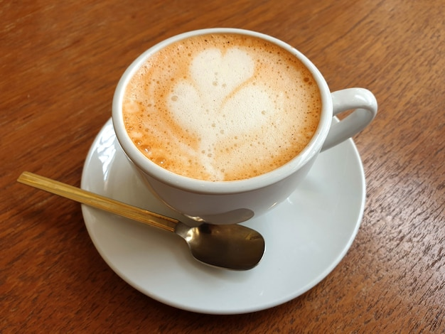 나무 테이블에 뜨거운 라떼 아트 커피 한 잔