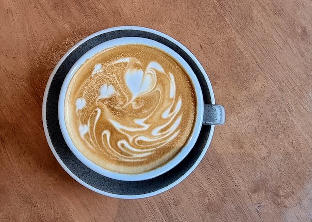 Чашка горячего кофе латте арт на деревянных фоне