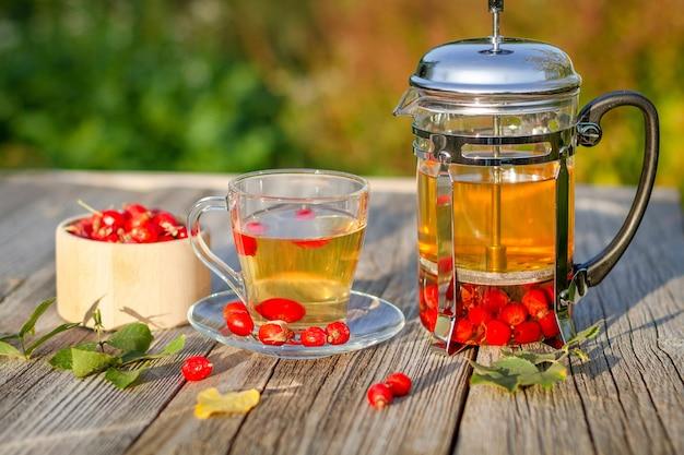 秋の庭の木製のテーブルに熱いローズヒップティーのカップ。