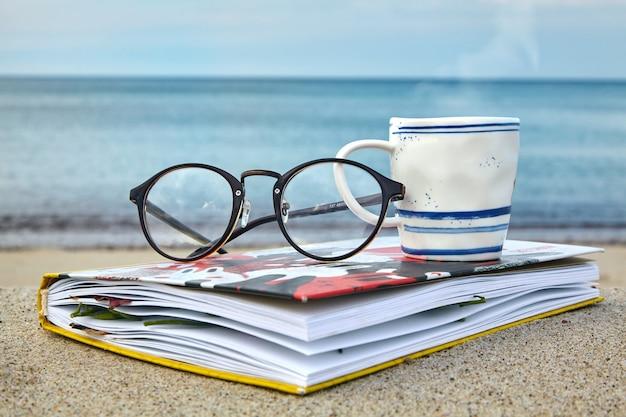 Чашка горячего чая, стаканы и блокнот с сушеными листьями на берегу моря. отдых у моря, релаксация