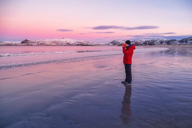 눈 덮인 북부 언덕을 배경으로 북극 해안에있는 한 남자의 손에 따뜻한 차 한잔. 멋진 극지 일몰. 여행 개념.