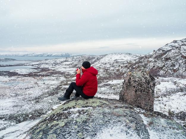 눈 덮인 북쪽 언덕의 극지방 언덕 위에있는 남자의 손에 따뜻한 차 한잔. 멋진 북극 풍경. 여행의 개념.