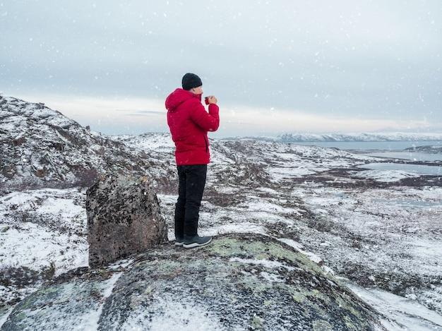 극지 언덕 위에있는 남자의 손에 뜨거운 차 한잔. 눈 덮인 북부 언덕. 멋진 북극 풍경. 여행의 개념.