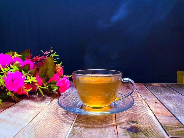 木製のテーブルにピンクのバラの花と朝の熱いお茶のカップ